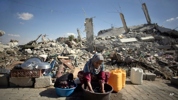 FILE - In this Wednesday, Oct. 1, 2014 file photo, a Palestinian woman washes clothes as she sits in front of the rubble of her family house in Khuzaa, southern of Gaza Strip. A U.N. aid agency that helps Palestinians in Gaza says that after numerous delays, it's ready to begin helping a small number of people rebuild their homes, destroyed in last summer's war in the coastal strip. (AP Photo/Khalil Hamra, File)