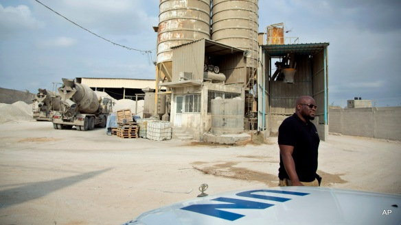 "FILE - In this Oct. 11, 2014 file photo, Keith Mathias-O'Chez, an inspector of building materials for the U.N. Relief and Works Agency, visits one of seven mixing concrete factories that are responsible for preparing the concrete for the U.N. projects in the Gaza Strip. Gaza reconstruction is moving at a ""snail's pace"" and at this rate, it would likely take 30 years to rebuild the extensive damage from last summer's Israel-Hamas war, a senior U.N. official said. Roberto Valent, the incoming area chief of a U.N. agency involved in reconstruction told The Associated Press on Wednesday, June 24, 2015 in an interview that the system is too slow and Israel must open Gaza's borders to allow for the speedy rebuilding or repair of 141,000 homes he said suffered minor to severe damage or were destroyed. (AP Photo/Khalil Hamra, File)"
